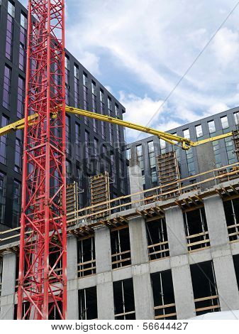 Highrise buildings under construction and yellow ready mix concrete pump to supply concrete mix up above