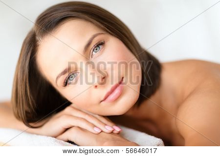 health, beauty, resort and relaxation concept - beautiful woman in spa salon lying on the massage desk