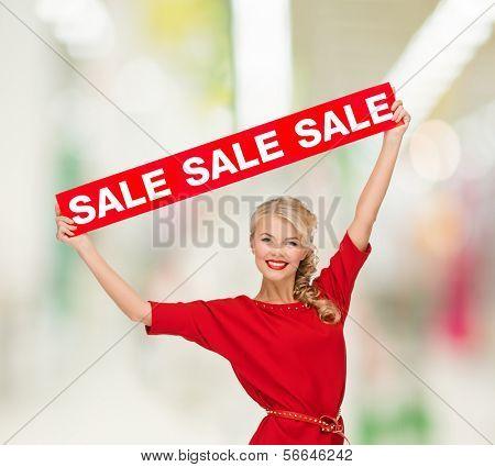 conceito de compra, venda, Natal e shopping - sorrindo a mulher de vestido com sinal vermelho venda no shopping m