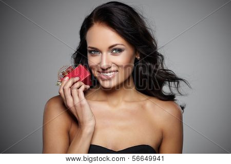 Smiling young woman holding a gift in a red box on grey background