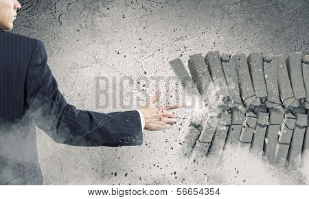 Businessman crushing pile of stones with finger touch