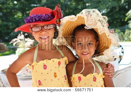 Two girls wearing hats at a tea party