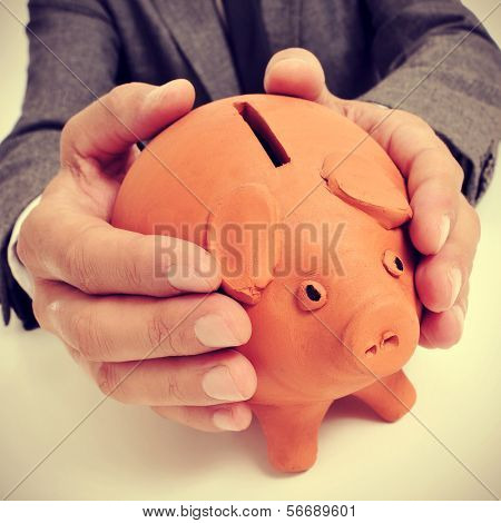 a man wearing a suit sitting in a desk with a piggy bank in his hands