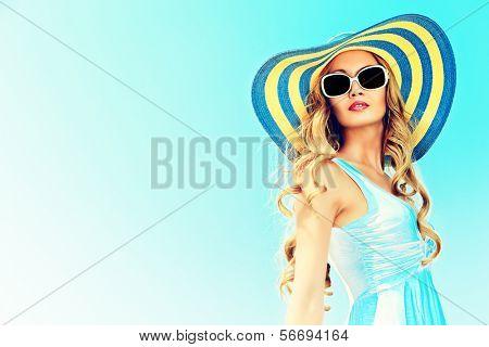 Impresionante joven elegante sombrero y gafas de sol posando sobre cielo.
