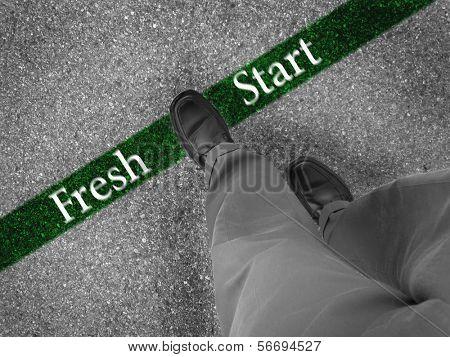 Man walking across a green line with words fresh start
