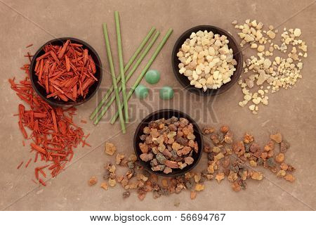 Frankincense, myrrh, sandalwood and incense sticks and cones over lokta paper background.