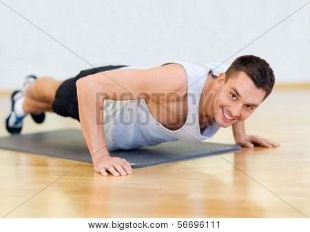 fitness, sport, training, gym and lifestyle concept - smiling man doing push-ups in the gym or at home