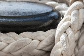 stock photo of bollard  - Detail of vessel part with bollard and mooring ropes - JPG