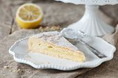 stock photo of sponge-cake  - Homemade lemon cake with cream and fresh lemon selective focus - JPG