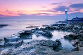 stock photo of lighthouse  - Lighthouse on a rocky sea beach at the sunset - JPG