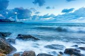 stock photo of beach-house  - Lighthouse on a rocky sea beach at the sunset - JPG