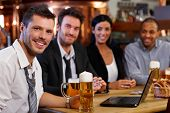 stock photo of mating  - Happy young office worker drinking beer at pub with colleagues - JPG