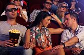 Young couple sitting in movie theater, girl flirting with boy on next seat.
