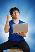 Crazy happy guy with computer laptop on blue background