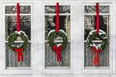 image of lace-curtain  - Christmas wreaths covered in snow hanging in front of lace curtained windows - JPG