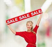 shopping, sale, christmas and mall concept - smiling woman in dress with red sale sign at shopping m