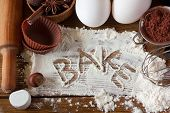 stock photo of ingredient  - Baking utensils spices and food ingredients on wooden board close - JPG