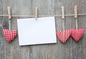 image of blank check  - Message and red hearts on the clothesline against wooden background - JPG
