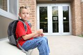 Boy student waiting outside of school