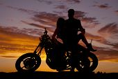 stock photo of down jacket  - A silhouette of a woman sitting on a motorcycle her man is looking down at her - JPG