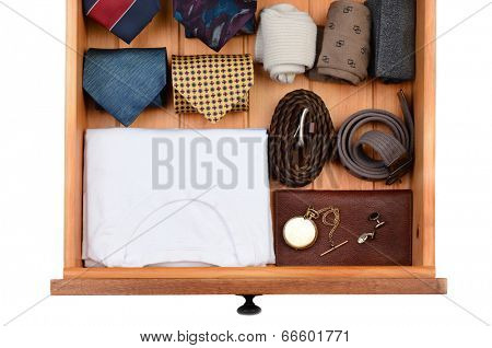 High angle shot of a dresser drawer with under shirts, belts, neck ties, socks, pocket watch and cuff links. Horizontal format isolated on white.