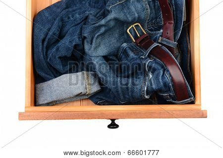 High angle shot of a pair of blue jeans crumpled up in a dresser drawer. Horizontal format isolated on white.