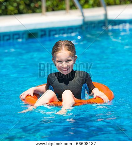 cute  little girl swims in a wetsuit with a lifeline in the pool in  summer