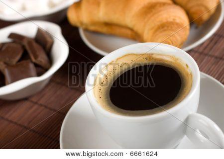 Tasse Kaffee serviert mit Croissants und Schokolade