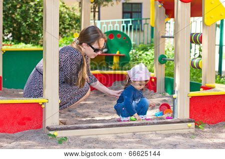 Mother And Little Daughter At Playground