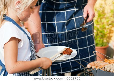 Dad and kid doing the BBQ