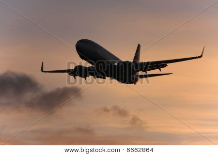 Silhouette of airliner at sunset.