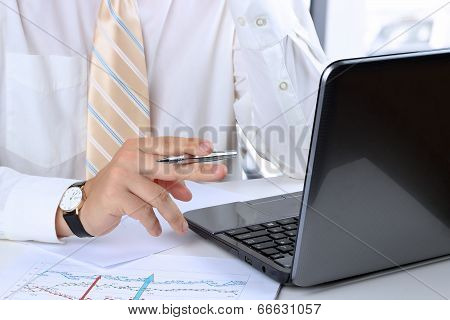 Young Businessman Working In The Office Sitting At His Desk,  Reading  Information On His Laptop