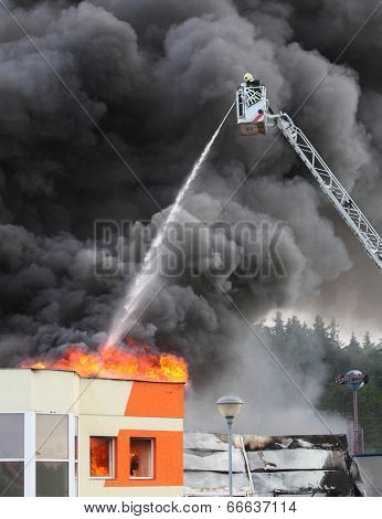 PILSEN, CZECH REPUBLIC - JUNE 12 2014: unidentified professional firefighters extinguishing burning factory. Fire department of Pilsen City.