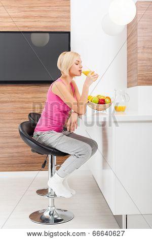 woman drink orange juice glass in her kitchen