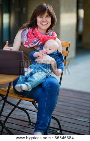 Young Working Mother With Little Son In A Cafe
