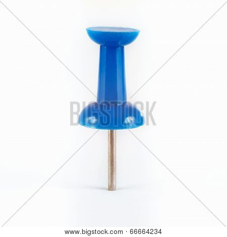 Blue pushpin stuck in the white paper closeup