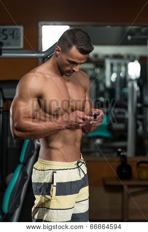 Young Man Texting While Fitness Sesion