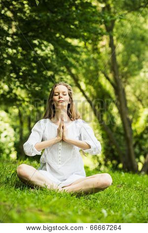 Yoga. Young Woman doing Yoga Exercises Outdoor