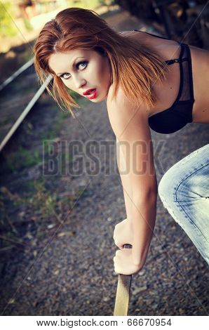 Beautiful Redhead Girl In Bra And Jeans Pulls A Railway Lever. Closeup