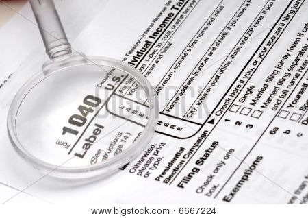 1040 income tax form and a magnifying glass