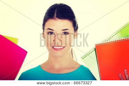 Portrait of a young beautiful female student holding workbooks.