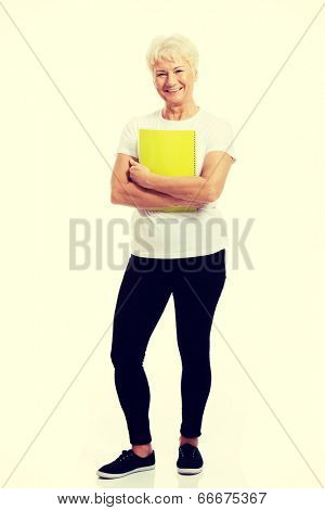 An old woman holding a workbook