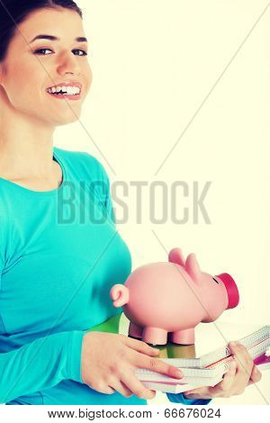 Casual student woman holding workbook and piggy-bank.
