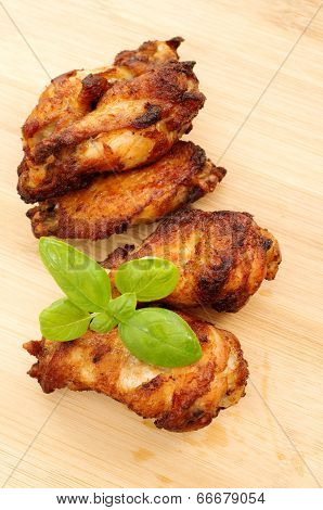 Deep Dried Chicken Wings On A Bamboo Cutting Board With Basil Leaves