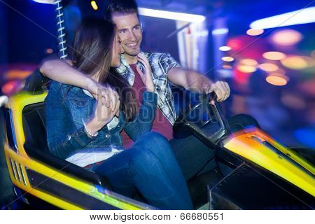 Young couple driving in a bumper car, dodgem ride