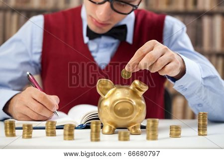 young accountant male counting money and putting in piggy bank