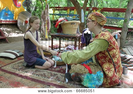 MUSKOGEE, OK - MAY 24: A group of teenagers dressed as traveling gypsies rest near cabins at the Oklahoma 19th annual Renaissance Festival on May 24, 2014 at the Castle of Muskogee in Muskogee, OK.