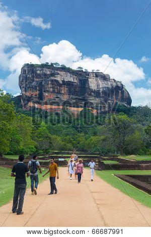 SIGIRIYA, SRI LANKA - 28 FEBRUARY, 2014: Tourists walking in garden complex with rock of Sigiriya as backdrop . Sigiriya is UNESCO listed World Heritage Site.