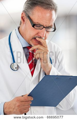 Senior doctor reading a case history