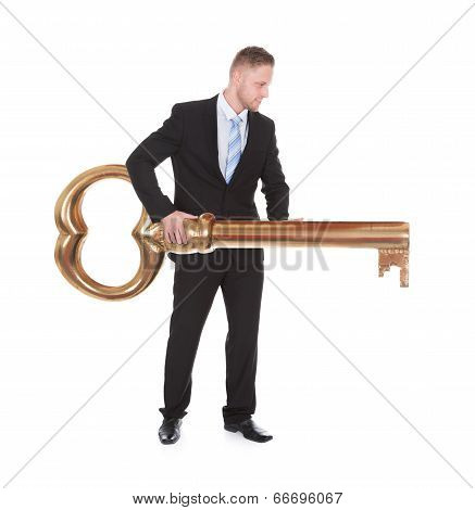 Businessman Carrying A Large Brass Key